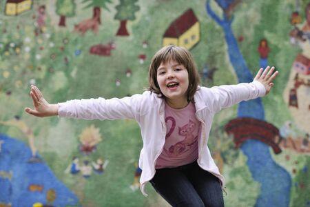 estilo urbano: ni�a feliz posando y saltando con estilo urbano abstracto pintura bacground est�  Foto de archivo