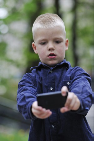 young blonde boy playing videogames outdoor in park Stock Photo - 7147329