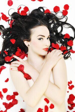 mujer con rosas: hermosa joven mujer desnuda con rosas aislados en blanco que representa el concepto de belleza