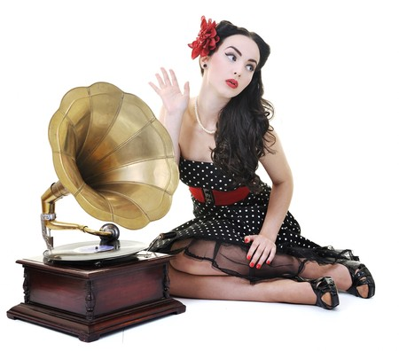pinup girl: pretty girl listening music on old gramophone isolated on white in studio Stock Photo