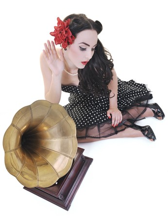 pin up: pretty girl listening music on old gramophone isolated on white in studio Stock Photo