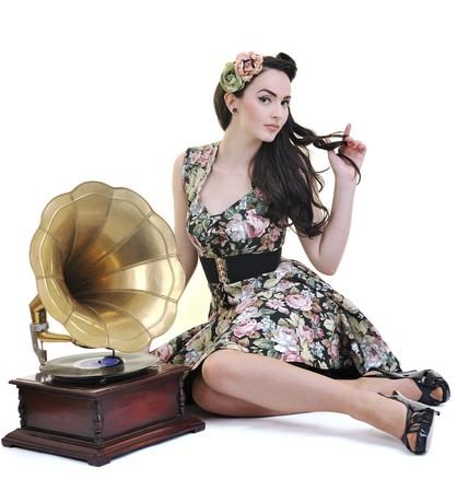 mooi meisje luisteren muziek op oude grammofoon geïsoleerd op wit in de studio