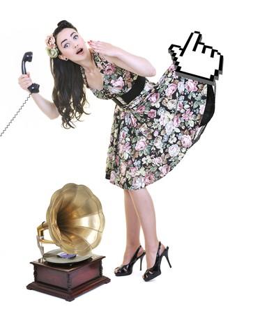 repondre au telephone: assez jeune femme parler par t�l�phone ancienne et de la fl�che de curseur de souris tient sa jupe