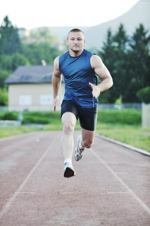 young healthy man run on athletic race sport track and representing concept of sort and speed photo