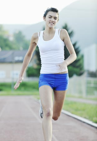 beautiful young woman exercise jogging and runing on athletic track on stadium at sunrise Stock Photo - 7204964