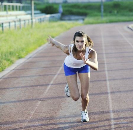 beautiful young woman exercise jogging and runing on athletic track on stadium at sunrise Stock Photo - 7205004