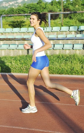 beautiful young woman exercise jogging and runing on athletic track on stadium at sunrise  Stock Photo - 7205046