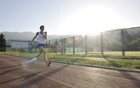sun track: beautiful young woman exercise jogging and runing on athletic track on stadium at sunrise