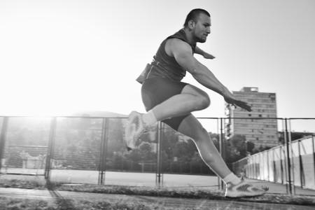 sudando: joven saludable ejecutar en la pista atl�tica de deporte y que representa a concepto de ordenar y velocidad