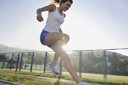 runing: beautiful young woman exercise jogging and runing on athletic track on stadium at sunrise