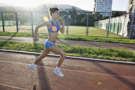 beautiful young woman exercise jogging and runing on athletic track on stadium at sunrise  photo