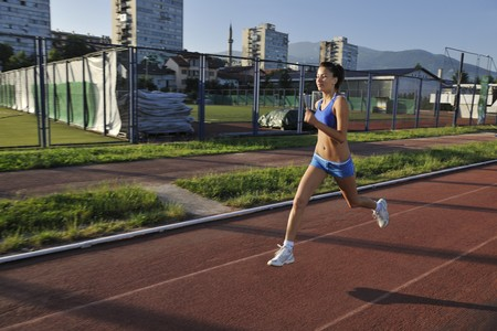 beautiful young woman exercise jogging and runing on athletic track on stadium at sunrise Stock Photo - 7205128