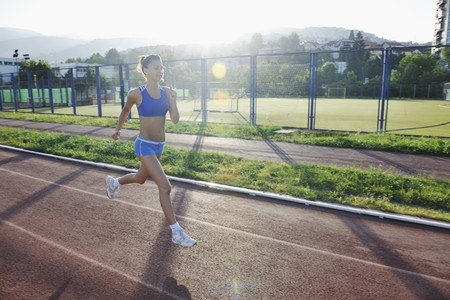 beautiful young woman exercise jogging and runing on athletic track on stadium at sunrise  Stock Photo - 7205130