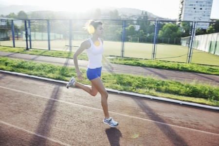 fast lane: ejercicio de la joven y bella mujer jogging y ejecutando en la pista de Atletismo en el estadio al amanecer