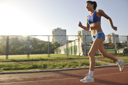 beautiful young woman exercise jogging and runing on athletic track on stadium at sunrise Stock Photo - 7205031