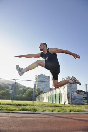 atleta corriendo: joven saludable ejecutar en la pista atl�tica de deporte y que representa a concepto de ordenar y velocidad