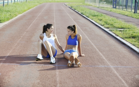 two girls relaxing on athletic race track Stock Photo - 17485425