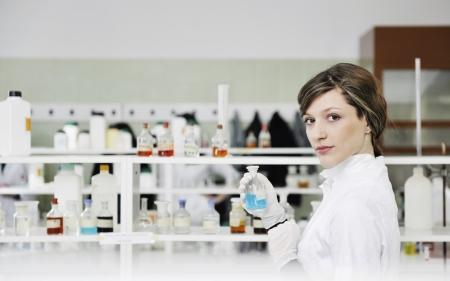 bata de laboratorio: clases de qu�mica de la ciencia con mujer joven estudiante en labaratory  Foto de archivo