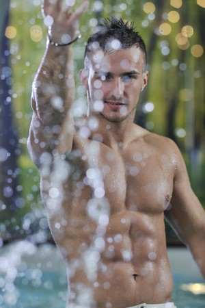 natural pool: young healthy good looking macho man model athlete at hotel indoor pool Stock Photo