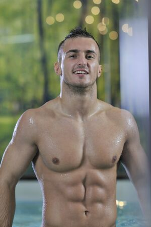 young healthy good looking macho man model athlete at hotel indoor pool Stock Photo - 7329006