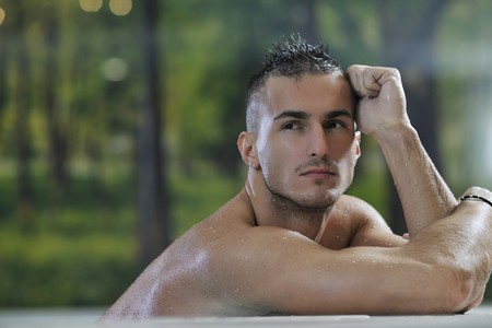 young healthy good looking macho man model athlete at hotel indoor pool Stock Photo - 7329047