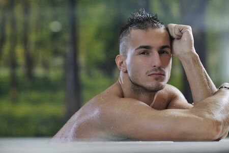 young healthy good looking macho man model athlete at hotel indoor pool Stock Photo - 7329035