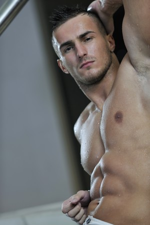 sexy shower: young healthy good looking macho man model athlete at hotel indoor pool Stock Photo
