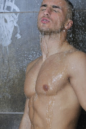 young good looking and attractive man with muscular body wet taking showe in bath with black tiles in background Stock Photo - 7286131
