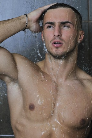 young good looking and attractive man with muscular body wet taking showe in bath with black tiles in background Stock Photo - 7286168