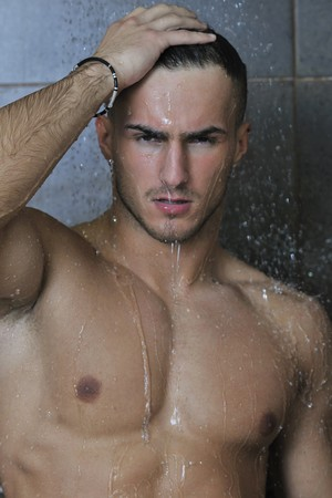 young good looking and attractive man with muscular body wet taking showe in bath with black tiles in background Stock Photo - 7329050