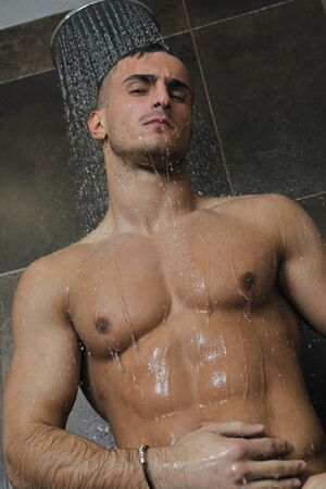young good looking and attractive man with muscular body wet taking showe in bath with black tiles in background Stock Photo - 7286134