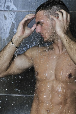 young good looking and attractive man with muscular body wet taking showe in bath with black tiles in background Stock Photo - 7329085