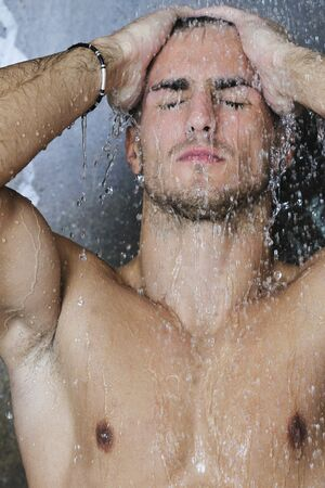 young good looking and attractive man with muscular body wet taking showe in bath with black tiles in background Stock Photo - 7329094