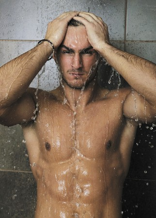 young good looking and attractive man with muscular body wet taking showe in bath with black tiles in background Stock Photo - 7329086