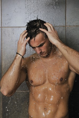 young good looking and attractive man with muscular body wet taking showe in bath with black tiles in background Stock Photo - 7286165