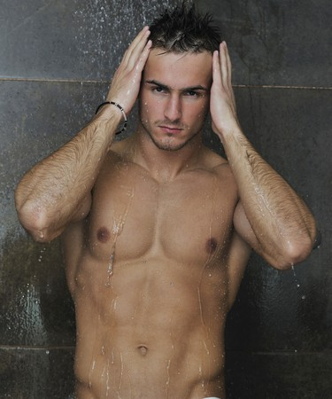 young good looking and attractive man with muscular body wet taking showe in bath with black tiles in background Stock Photo - 7221203