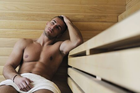 happy good looking and attractive young man with muscular body  relaxing in sauna hot photo