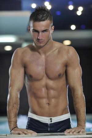 jóvenes saludables buen aspecto hombre macho modelo atleta en la piscina cubierta del hotel