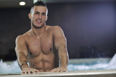 shower man: young healthy good looking macho man model athlete at hotel indoor pool Stock Photo