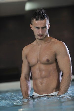 young healthy good looking macho man model athlete at hotel indoor pool photo