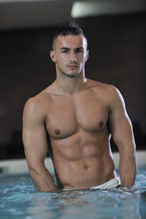 young healthy good looking macho man model athlete at hotel indoor pool Stock Photo - 7329051