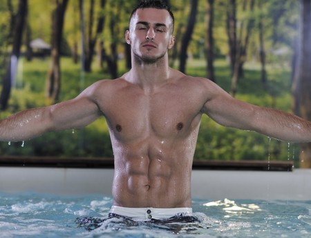 tanned: young healthy good looking macho man model athlete at hotel indoor pool Stock Photo