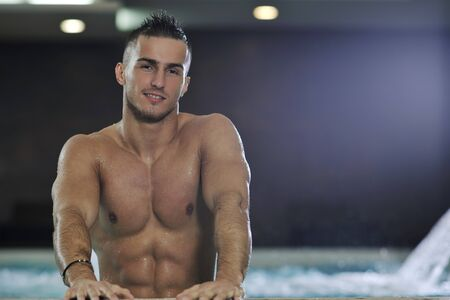 young healthy good looking macho man model athlete at hotel indoor pool Stock Photo - 7329032