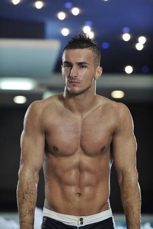 jonge gezonde goed uitziende macho man model atleet op indoor zwembad van het hotel