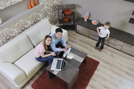 young happy family at bright and modern living room puting money in piggy bank and working on laptop computer on home finance Stock Photo - 13340230