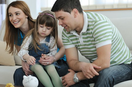young parrent at home with beautiful child make savings and put coins money in piggy bank photo