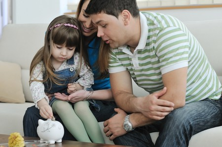 put: young parrent at home with beautiful child make savings and put coins money in piggy bank