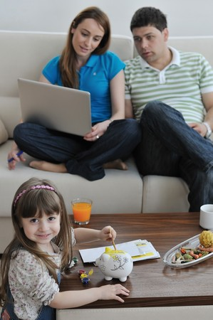 young parrent at home with beautiful child make savings and put coins money in piggy bank Stock Photo - 7287854