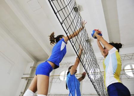 pelota de voley: deporte juego de voleibol con grupo de ni�as interiores en la arena de deporte