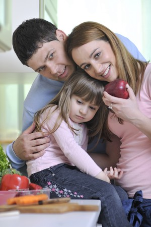 happy young family have lunch time with fresh fruits and vegetable food in bright kitchen photo